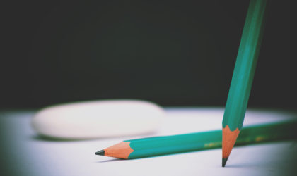 Green pencils and eraser on school board desk background. Selective Focus